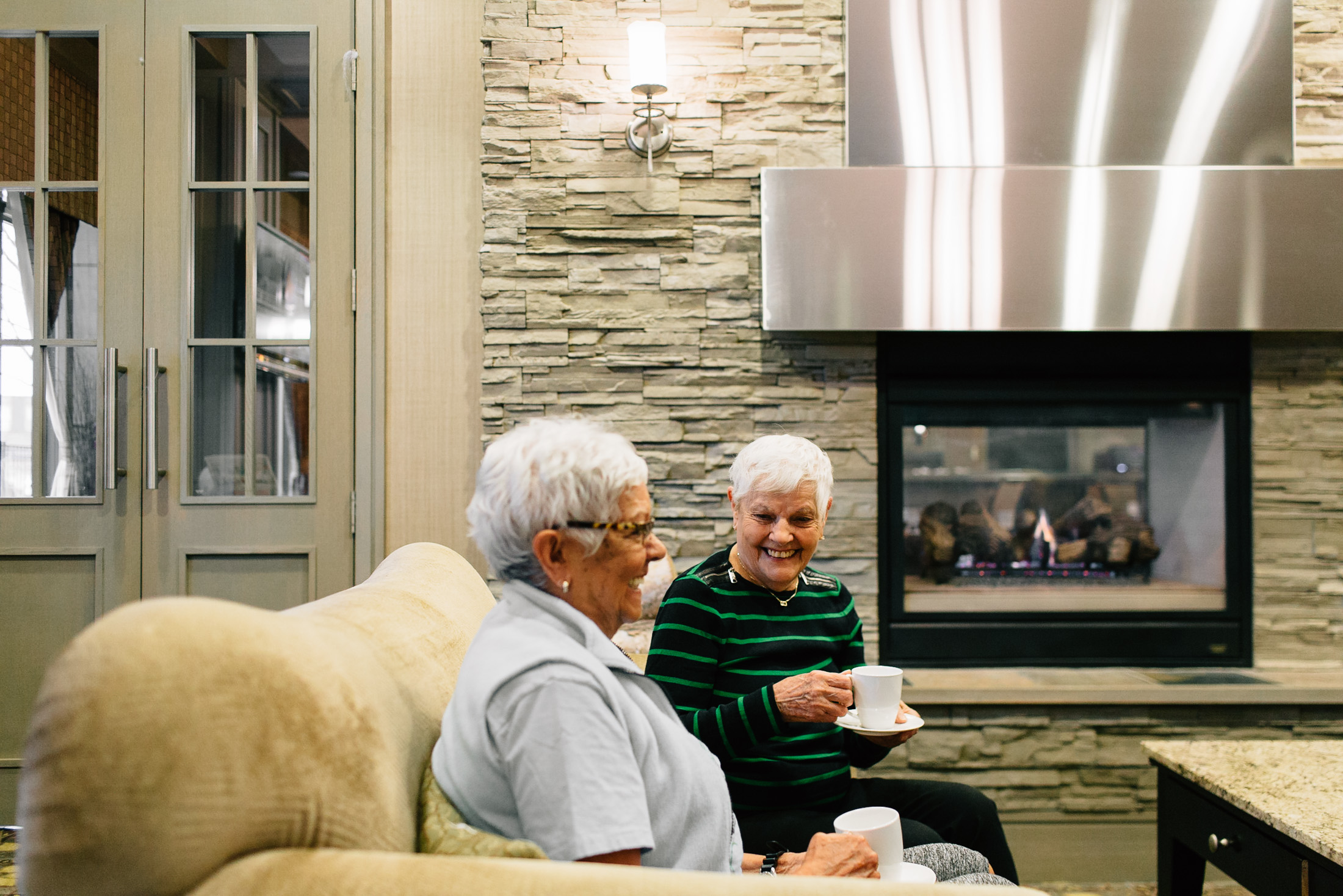 Seniors enjoying a cup of coffee by the fire